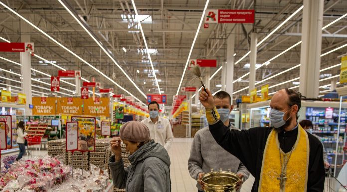 As a priest in the mask of the consecrated 30,000 cakes in the supermarkets of Novosibirsk
